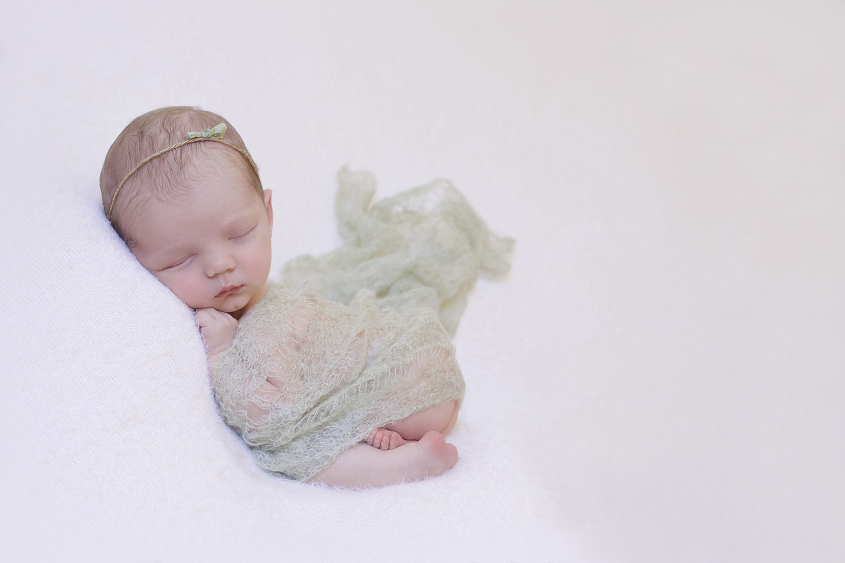 Newborn baby girl sleeping on cream blanket with green knit layer and greenbow tieback