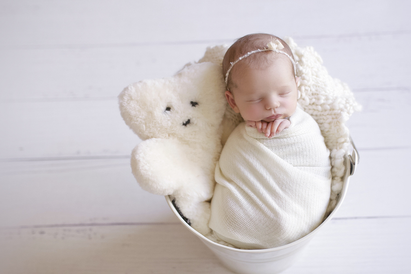 Newborn baby girl sleeping in cream bucket with cream knit layer and cream wrap and tieback and bear soft toy on white wooden floor