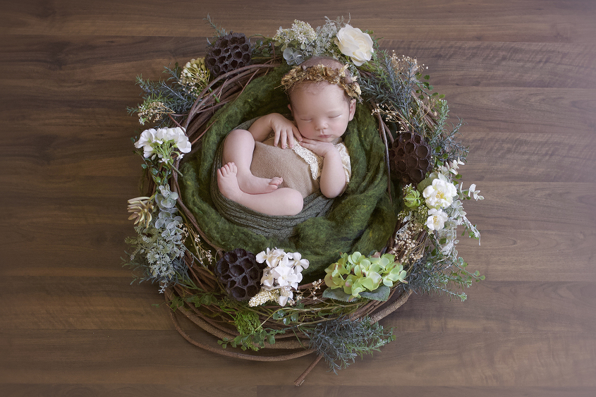 Newborn baby girl sleeping in brown cream and green flower nest wearing brown lace romper wearing brown flower crown on wooden floor