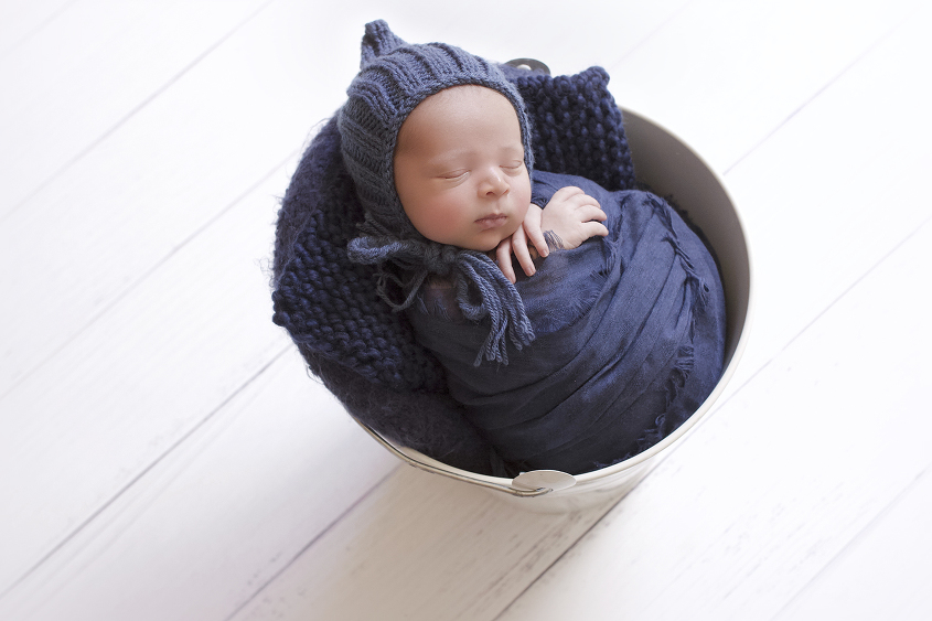 Newbonr baby boy sleeping in cream iron bucket wrapped in blue blanket with blue knit layer and bonnet on white wooden floor