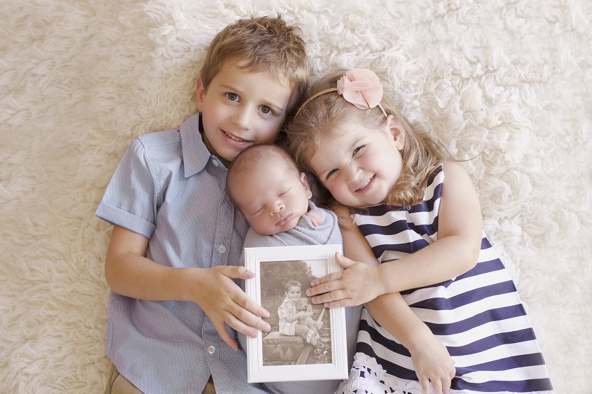 Newborn baby boy wrapped in blue wrap being held by three year old boy and two year old girl on cream fur holding photograph of deceased sibling in a frame