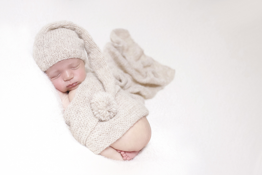 Newborn baby boy sleeping on cream blanket with cream knit layer and knit sleepy bonnet