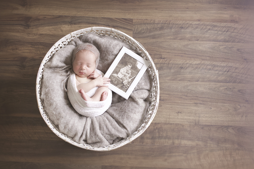 Newborn baby sleeping in round white cane basket with brown felt and white wrap and brown bonnet holding frame of deceased toddler sibling on wooden floor
