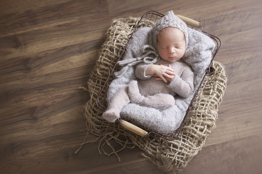 Newborn baby boy in wire farmers basket with grey blanket and romper and bonnet on hessian layer on wooden floor