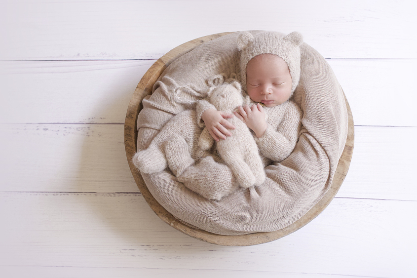 Newborn baby boy sleeping in round wooden bowl wearing cream knit romper and bear bonnet with knit bear on white wooden floor