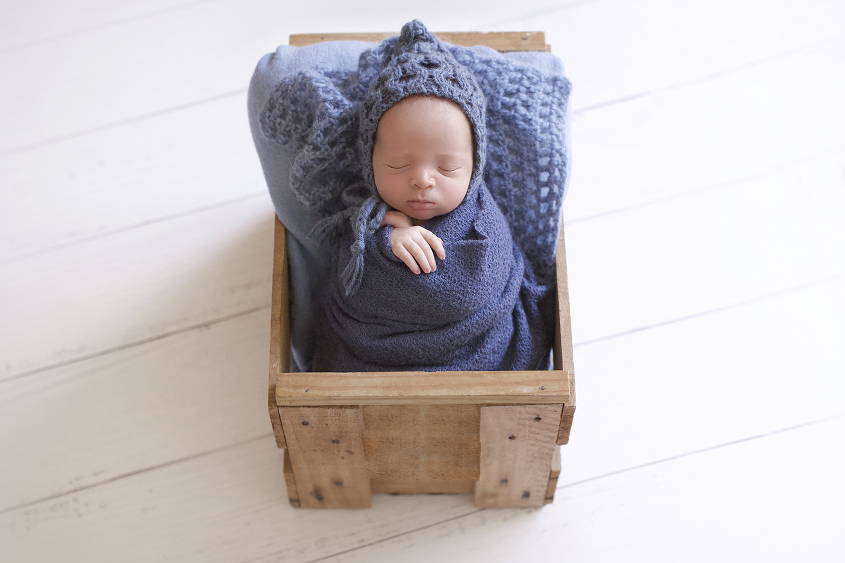 Newborn baby sleeping in wooden crate wrapped in blue blanket with blue knit layer and wrap and bonnet on white wooden floor