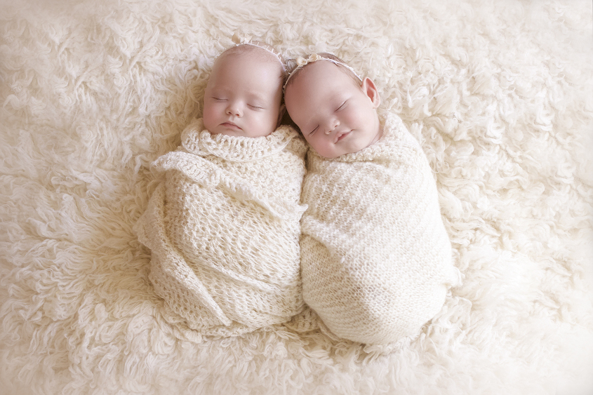 Baby twin girls sleeping wrapped in cream knit blankets on cream fur with bow tiebacks