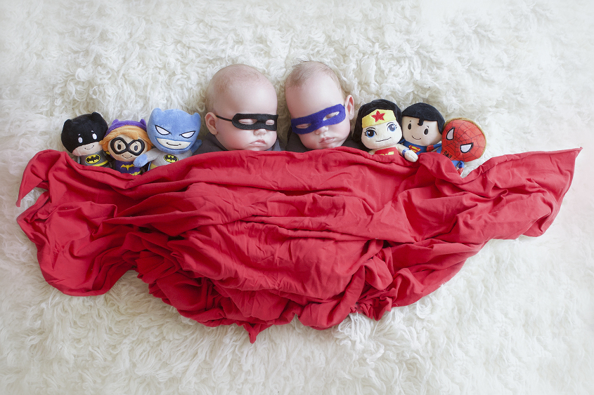 Newborn twin girls wrapped in grey blankets wearing superhero masks surrounded by soft toy super hero dolls wrapped in a red blanket on cream fur