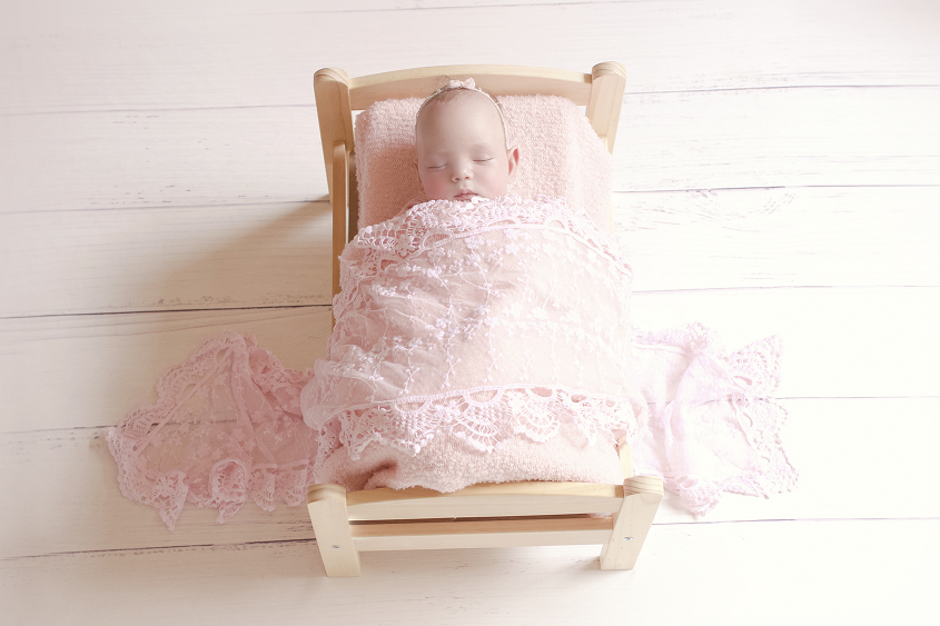 Newborn baby girl sleeping in wooden bed with pink blanket and lace wrap and headband on white wooden floor