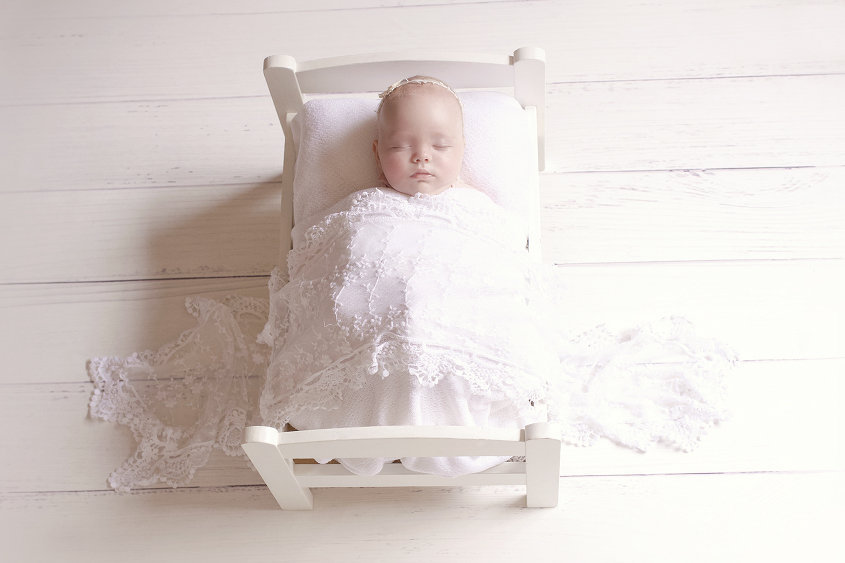 Newborn baby girl sleeping in white wooden bed with white blanket and lace wrap and headband on white wooden floor