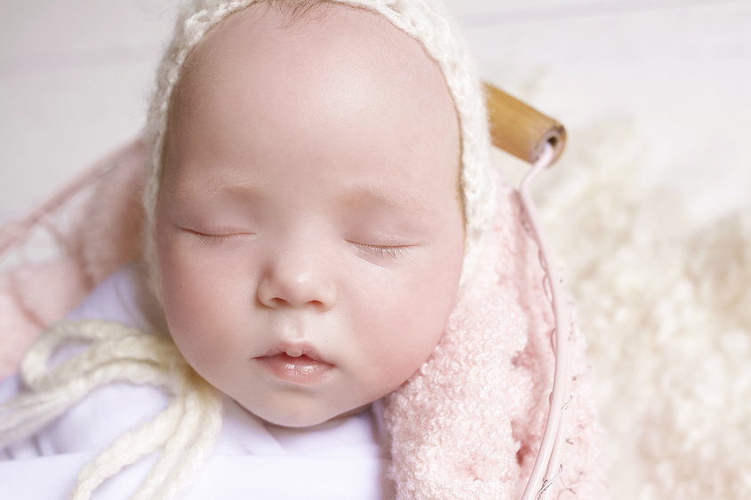 Newborn baby girl sleeping in farmers basket with pink blanket and wrap and felt and knit bonnet on white wooden floor