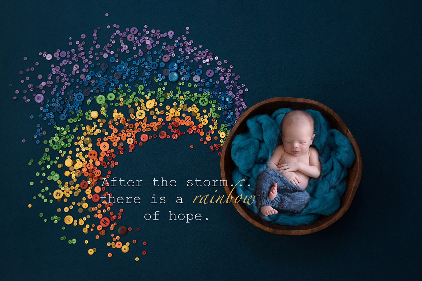 Newborn baby boy sleeping in round wooden bowl with teal felt wearing teal pants on teal back drop with rainbow made of buttons