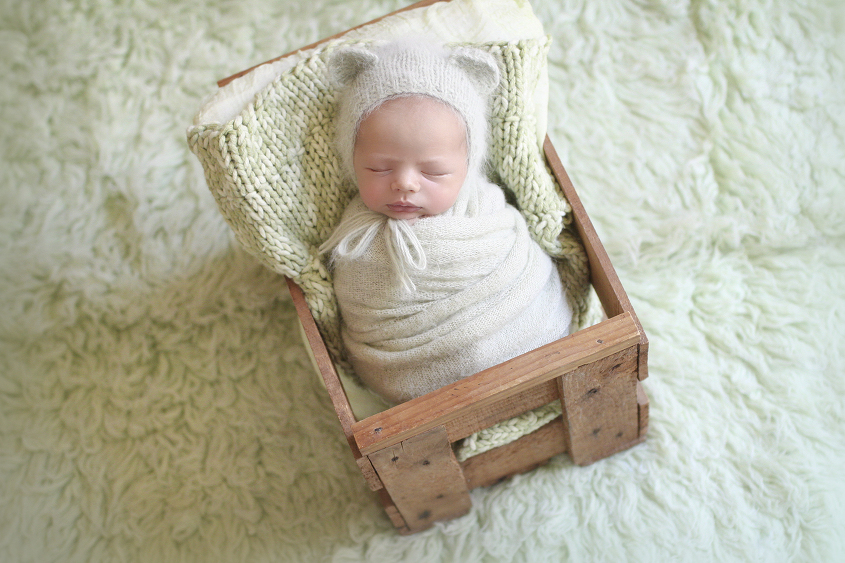 Newborn baby boy sleeping in wooden crate on green fur wrapped in green blanket with green knit layer and bear bonnet