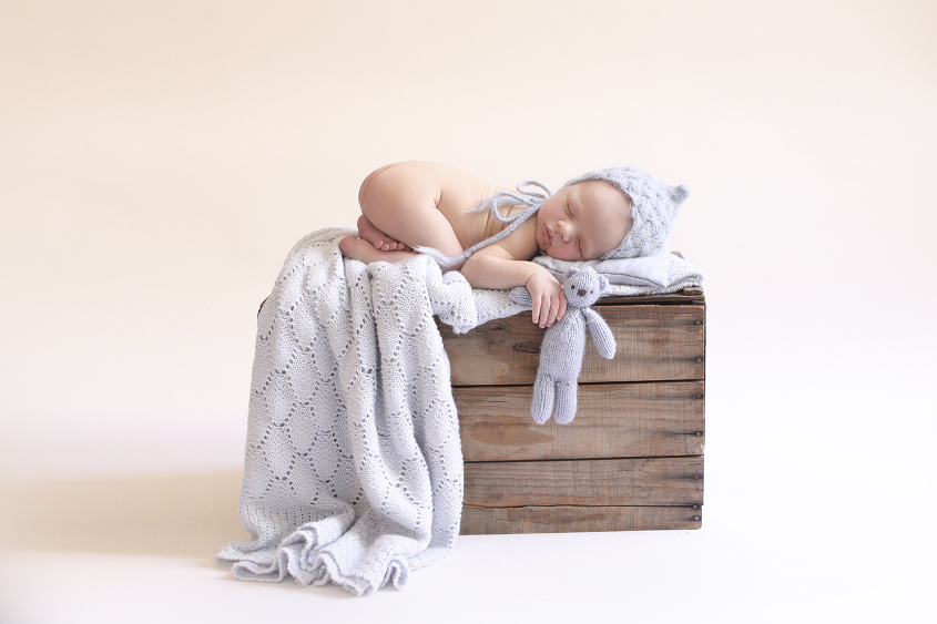 Newborn baby boy sleeping on wooden crate with blue blanket and knit bonnet and teddy