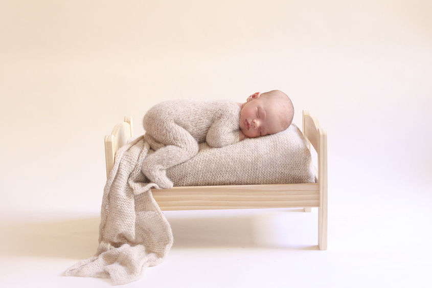 Newborn baby boy sleeping on wooden bed with cream knit wrap and wearing cream knit romper