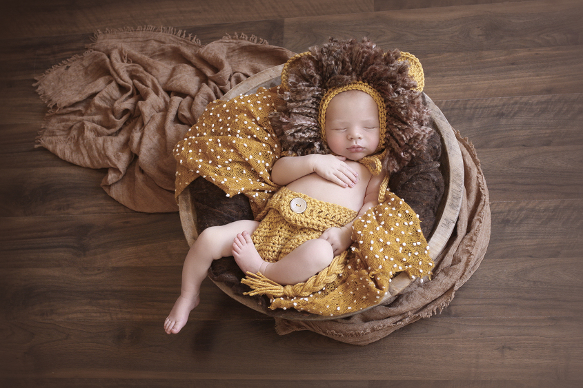 Newborn baby boy sleeping in round wooden bowl wearing knit lion outfit with brown felt and mustard blanket and wrap on wooden floor