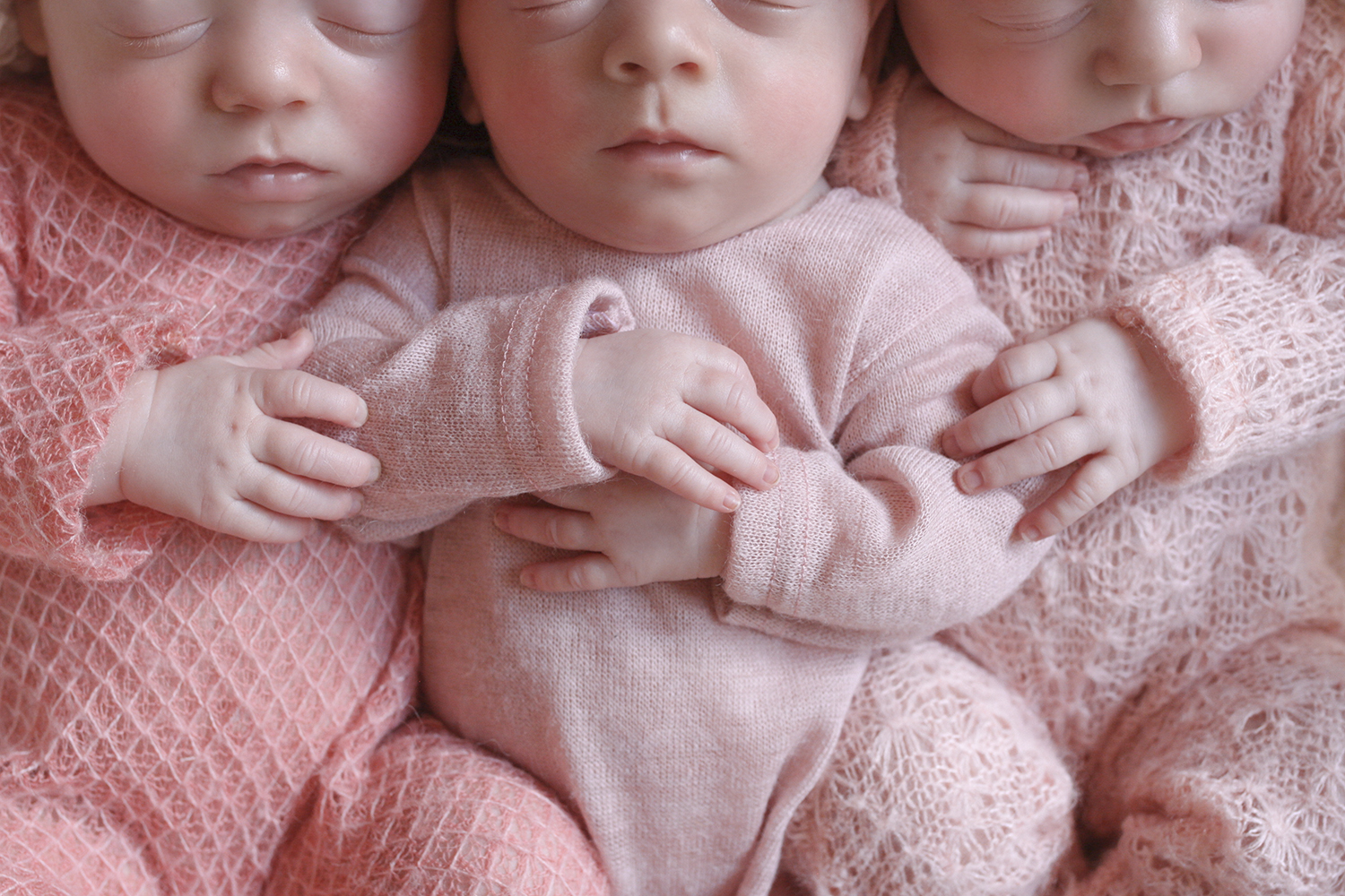 Newborn triplet baby girls wearing pink rompers and tiebacks in a white cane basket with white blanket inside and pink blanket underneath on white wooden floor