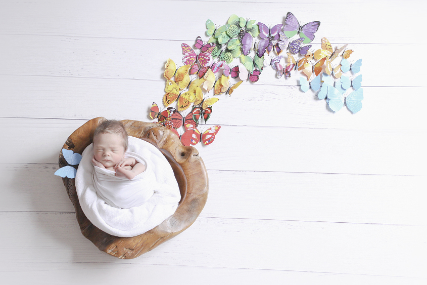 Newborn baby boy sleeping wrapped in white wrap in wooden log bowl with white blanket on white wooden floor with butterflies in rainbow shape