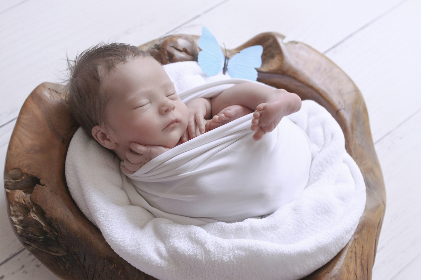 Newborn baby boy sleeping wrapped in white wrap in wooden log bowl with white blanket on white wooden floor with blue butterfly