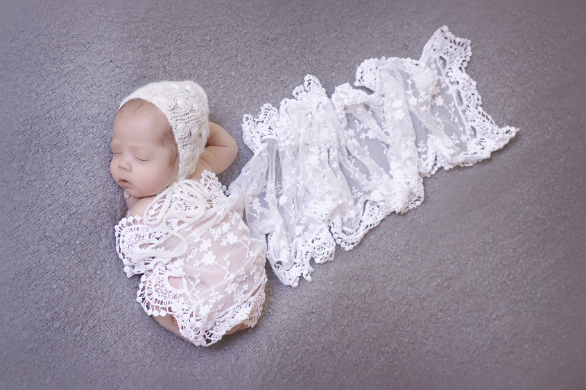 Newborn baby girl sleeping on grey blanket with white lace wrap and white knit bonnet