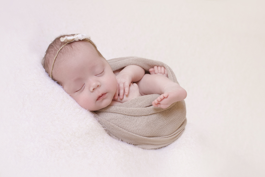 Newborn baby girl sleeping on cream blanket with brown lace knit wrap and tieback