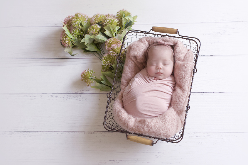 Newborn baby girl sleeping in farmers basket with pink blanket and wrap and bow tieback and flowers on white wooden floor