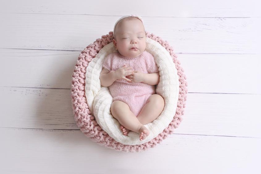 Newborn baby girl sleeping in pink crochet basket wearing pink romper with cream blanket on white wooden floor