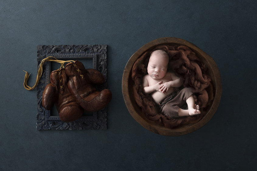 Premature baby sleeping in round wooden bowl with brown fluff wearing brown shorts on blue backdrop with teal frame and boxing gloves
