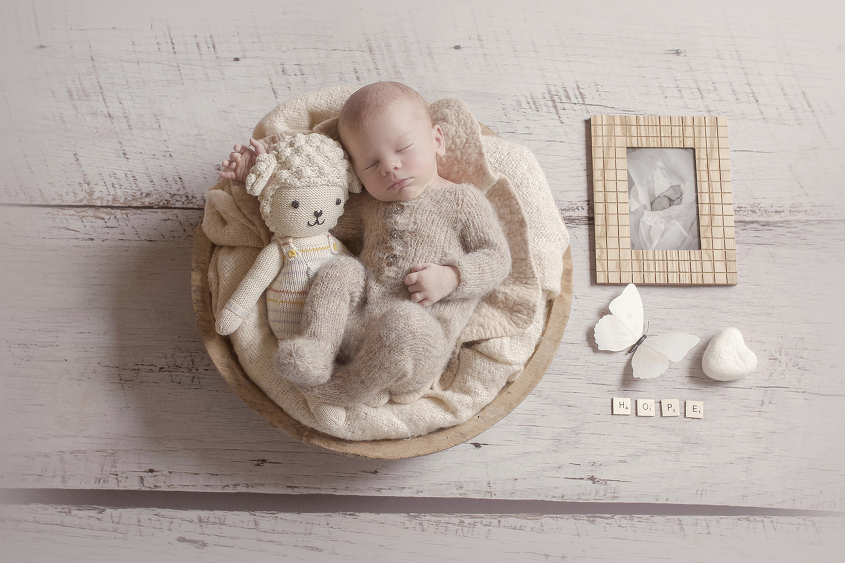Newborn baby boy sleeping in round wooden bowl with cream blanket and knit romper cuddling sheep toy on wooden floor with framed photo of stillborn baby sibling and butterfly and felt heart and words hope