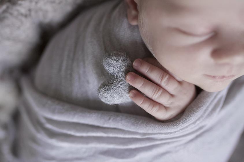 Newborn baby boy sleeping in cream bucket with grey wrap and felt layer on white wooden floor and grey felt heart