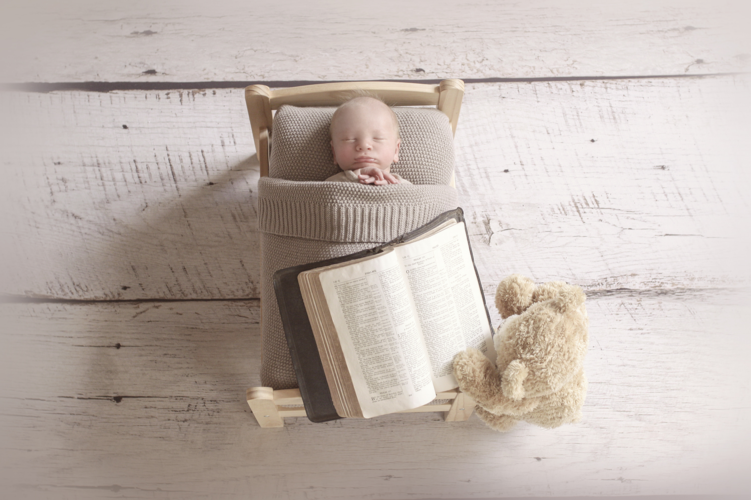 Newborn baby sleeping in wooden bed with brown blanket on wooden floor with teddy bear reading bible