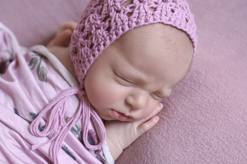 Newborn baby girl sleeping on pink blanket with purple flower wrap and knit bonnet
