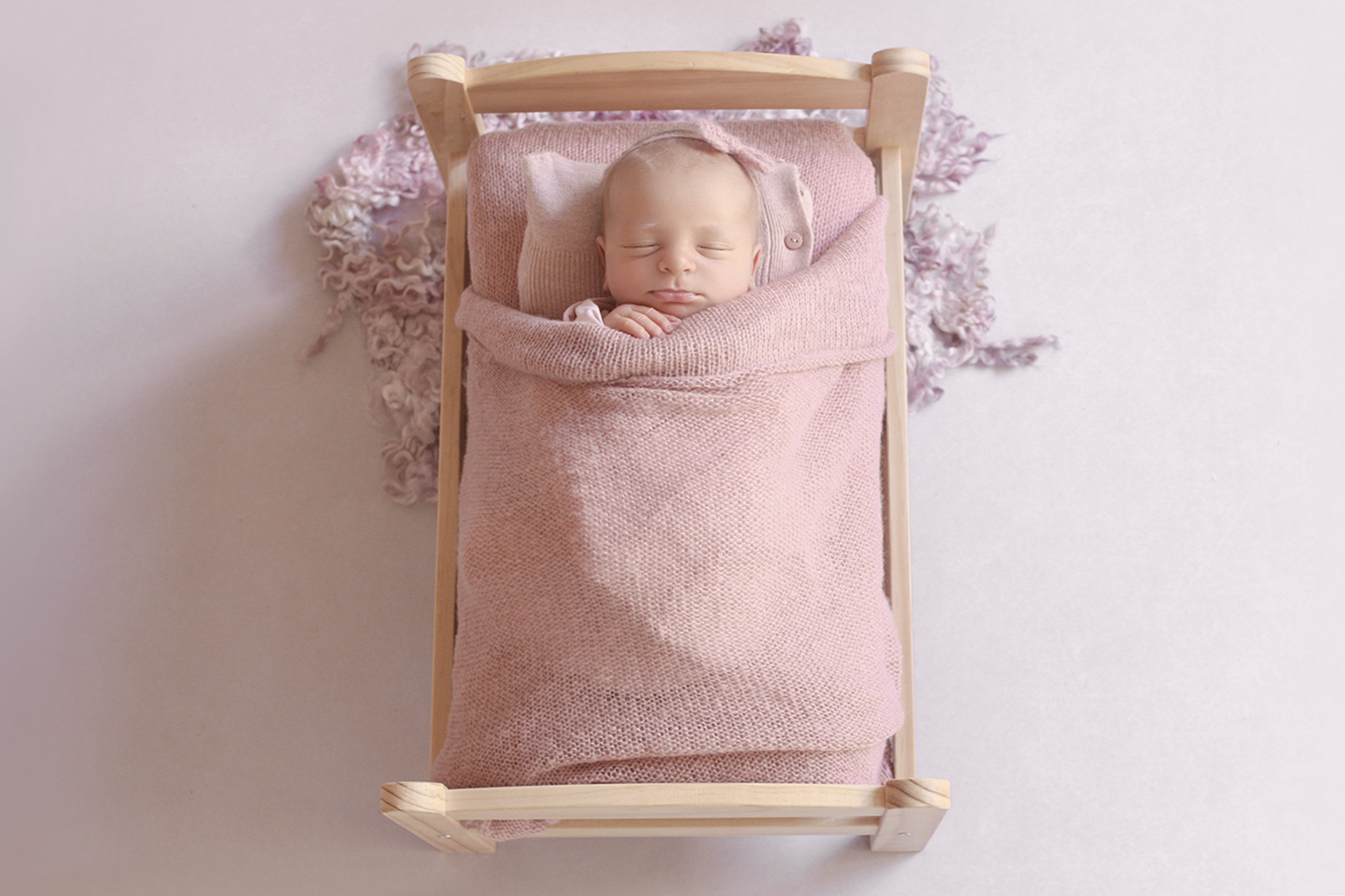 Newborn baby girl wrapped in pink wrap sleeping in wooden bed with pink blanket and pillow and tieback and curly felt layer