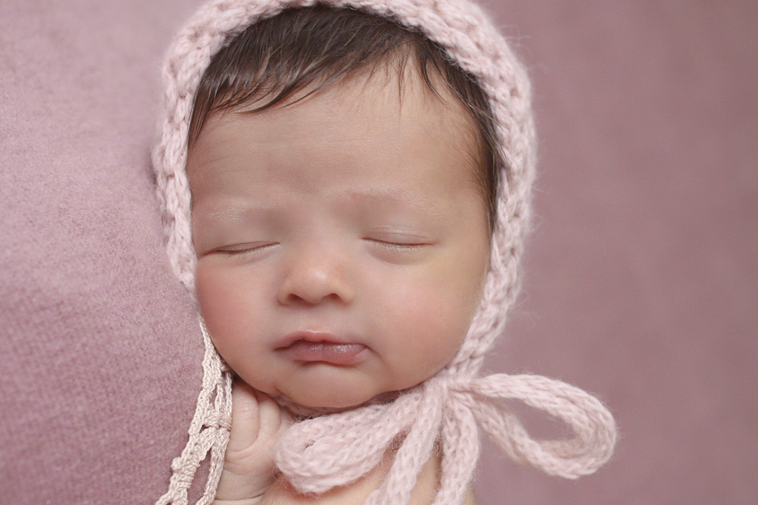 Newborn baby girl sleeping on pink blanket with pink lace and knit bonnet