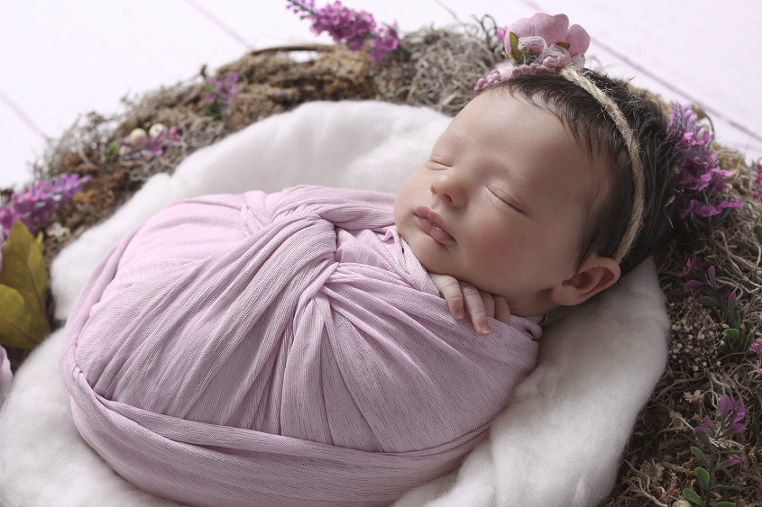 Newborn baby girl sleeping in lilac flower nest with cream fluff on white wooden floor wrapped in pink wrap with pink flower tieback