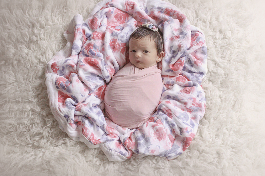 Newborn baby girl wrapped in pink blanket with pink and purple blanket on cream fur with pink flower tieback