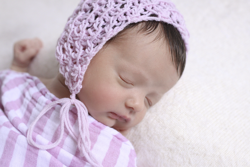 Newborn baby girl sleeping on cream blanket with pink stripe wrap and knit bonnet