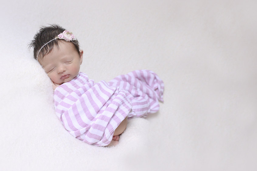 Newborn baby girl sleeping on cream blanket with pink stripe wrap and tieback