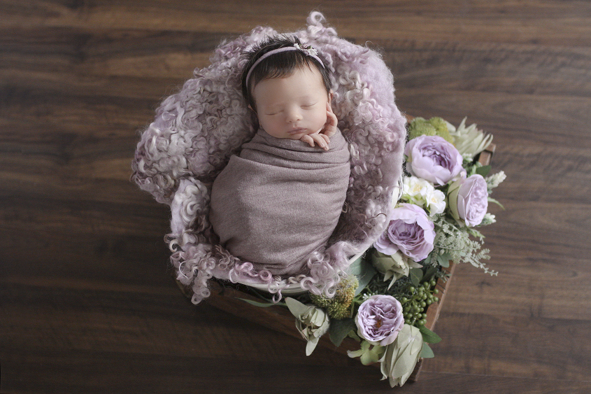 Newborn baby girl sleeping in cream bucket with purple curly felt and wrap and tieback in wooden drawer with purple flowers on wooden floor