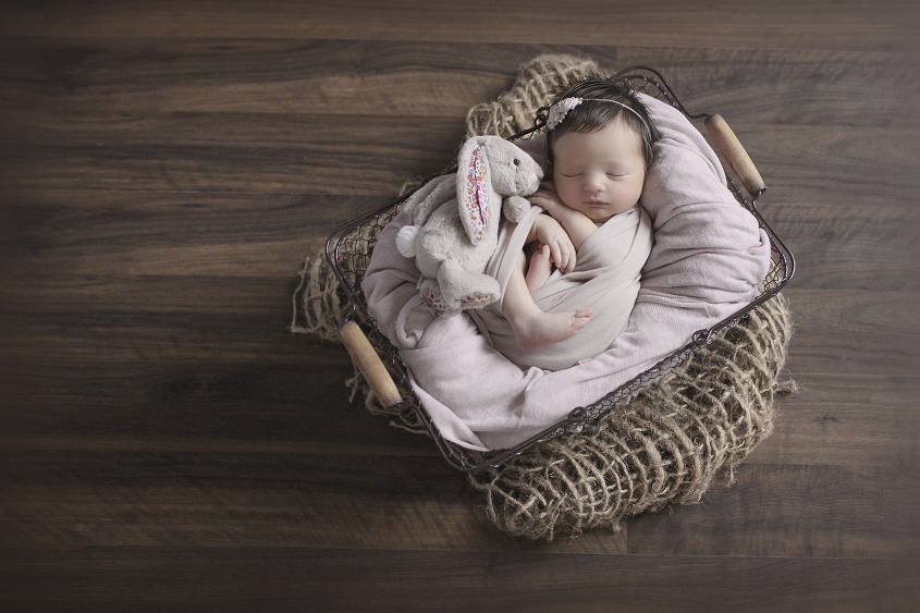 Newborn baby girl sleeping in farmers basket with dusty pink blanket and wrap on hessian layer on wooden floor with bunny toy and pink tieback