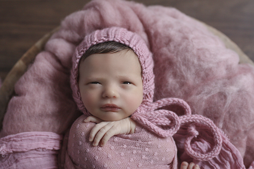 Newborn baby girl sleeping in round wooden bowl with pink fluff and wrap and bonnet on wooden floor