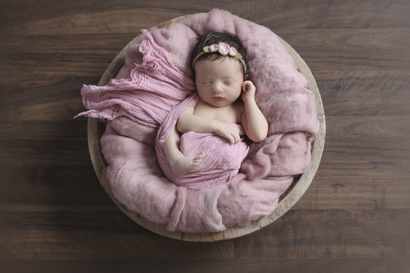 Newborn baby girl sleeping in round wooden bowl with pink fluff and wrap and tieback on wooden floor