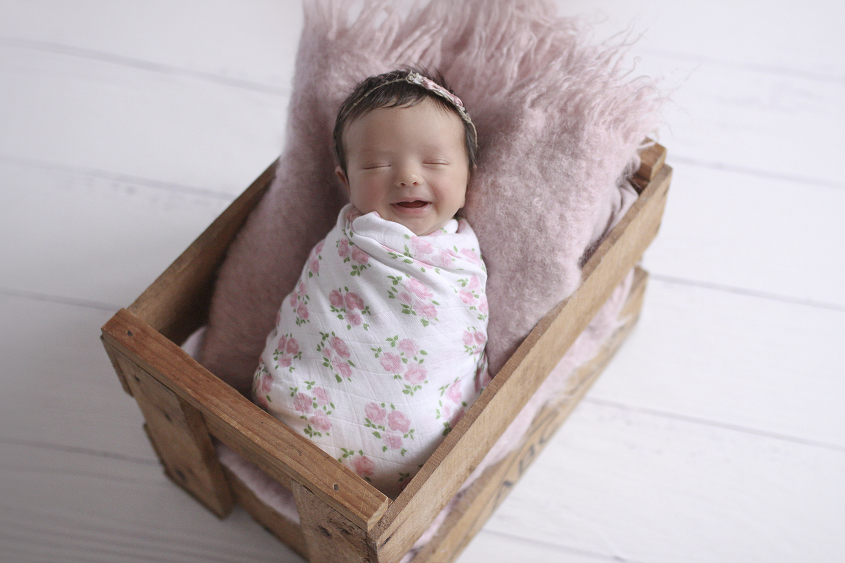 Newborn baby girl sleeping in wooden crate with pink blanket and pink and white flower wrap and tieback on white wooden floor
