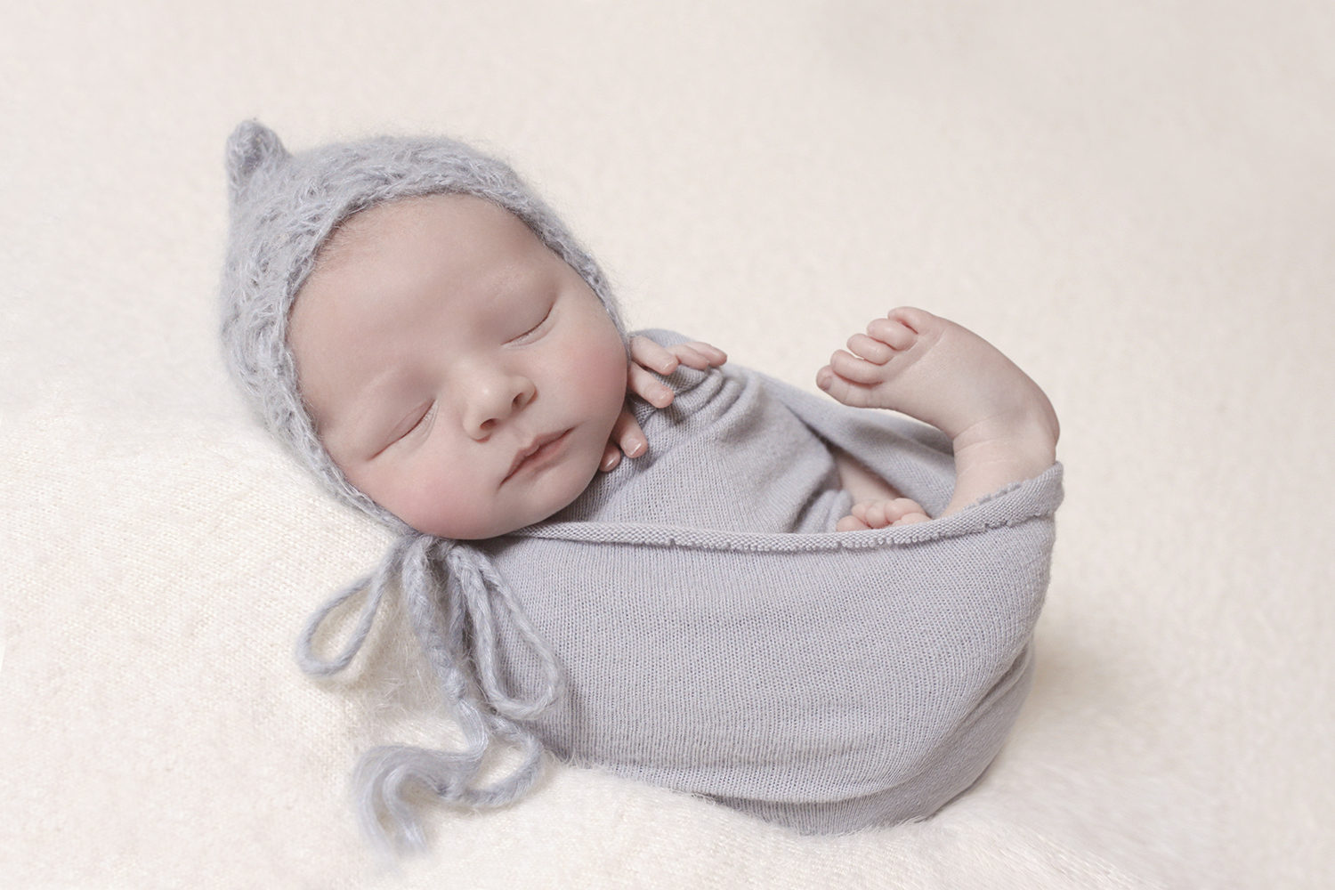 Newborn baby boy sleeping on cream blanket wrapped in blue wrap and blue knit bonnet