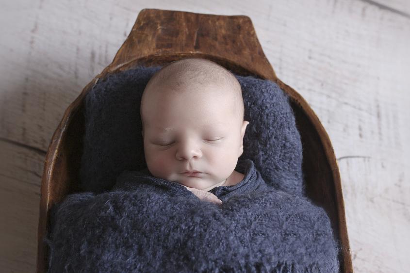 Newborn baby boy sleeping in wooden trench bowl with dark blue blanket on wooden floor