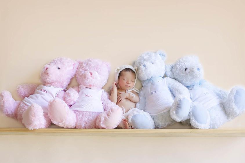 Newborn baby boy sleeping on shelf wearing bear ear bonnet beside two big blue bears and two pink bears