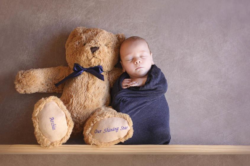 Newborn baby wrapped in blue wrap sitting on shelf beside bear