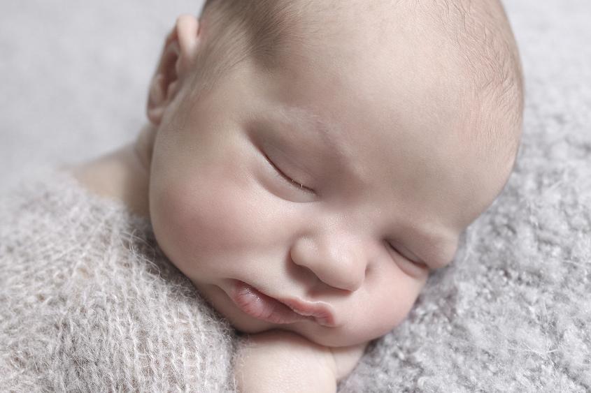 Newborn baby boy sleeping on grey blanket wearing grey knit bear romper