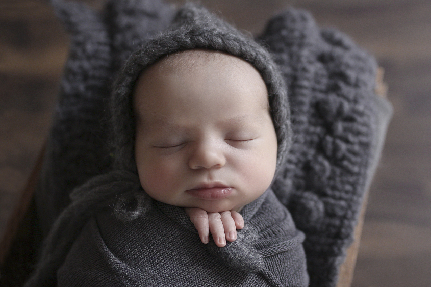 Newborn baby boy sleeping in wooden crate with grey blanket and knit layer and bonnet and felt heart on wooden floor