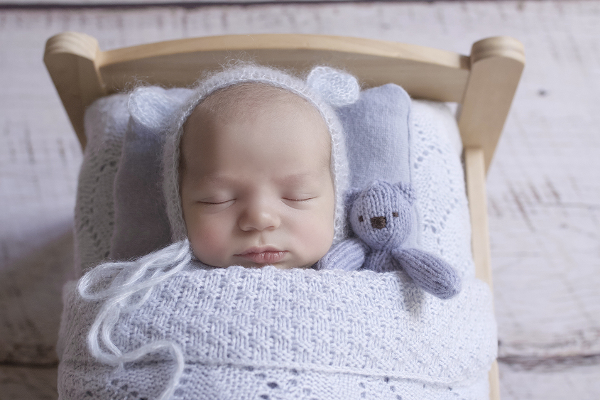Newborn baby boy sleeping in wooden bed with light blue knit blanket and bonnet and pillow and soft bear toy
